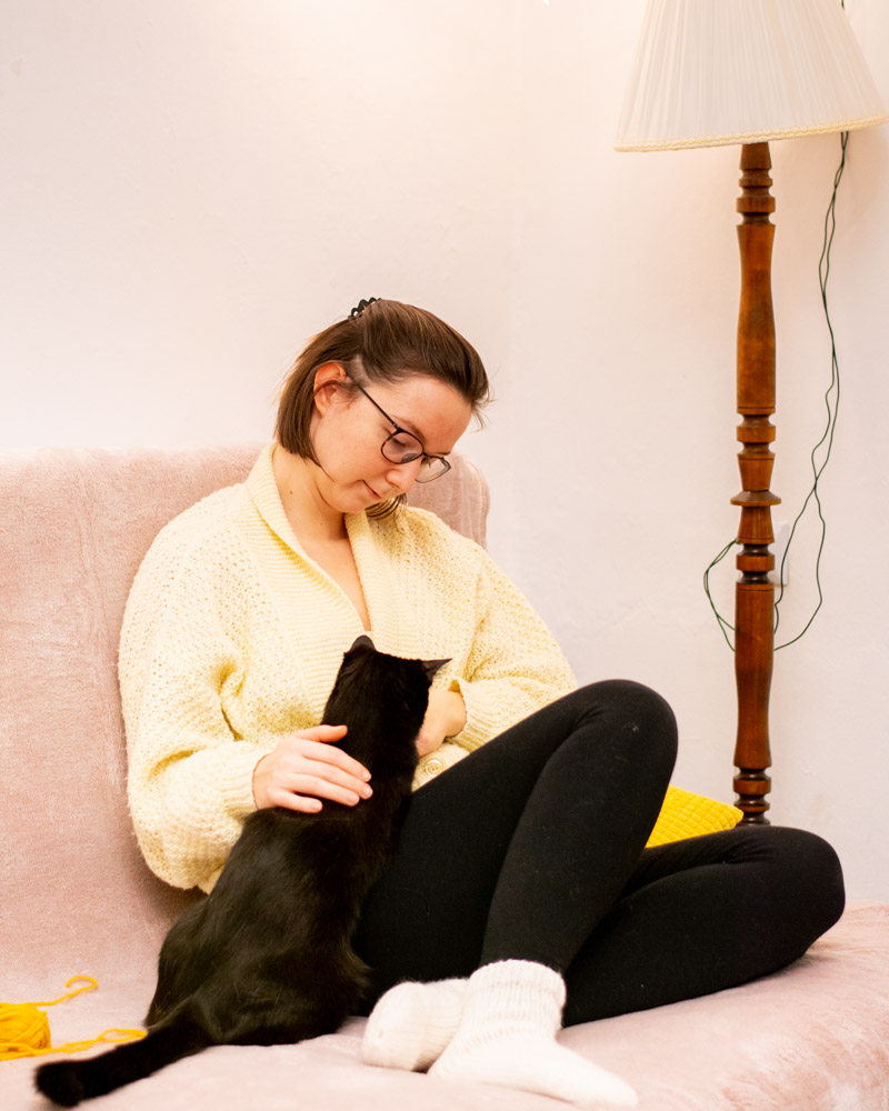 kobieta siedzi na sofie w białych skarpetkach i głaszcze czarnego kota